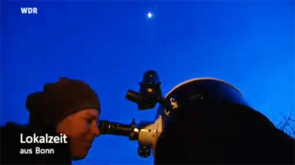 Eine Sternfreundin blickt durch ein Teleskop auf den Mond und auf Jupiter