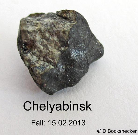 Ein Bruchstück des Chelyabinsk-Meteoriten. Typisch für frisch gefallene Chondriten sind die nahezu schwarze Schmelzkruste und die hellen Chondren im Innern, (c) D. Bockshecker